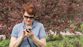 Elderly woman typing text on mobile phone. Medium shot of senior woman standing outdoors in apple blossom, web browsing smartphone. Concept of modern technology stock video footage