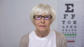 Elderly woman upset with sight examination taking off spectacles, cataract risk stock video