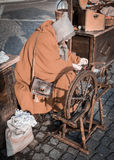 Elderly woman uses the cocoons of silkworms to spin. Royalty Free Stock Photography