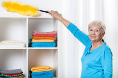 Elderly woman using duster Stock Photo