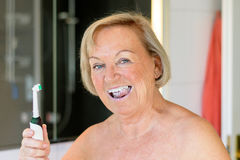 Elderly woman using an electric toothbrush Stock Photos