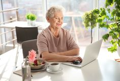 Elderly woman using laptop while having breakfast Royalty Free Stock Images