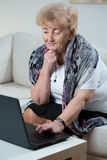 Elderly woman using laptop Royalty Free Stock Photos