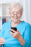 Elderly woman using mobile phone. Elderly woman during using mobile phone application royalty free stock photography
