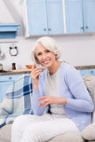 Elderly woman using mobile phone at home Royalty Free Stock Photo