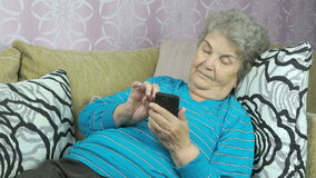Elderly woman using a mobile phone. Indoors stock footage