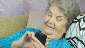 Elderly woman using a mobile phone stock footage