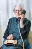 Elderly woman using the phone indoors Stock Image