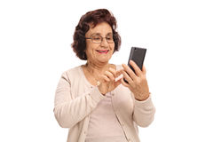 Elderly woman using a phone and smiling Stock Photo