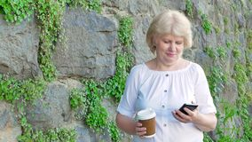 Elderly woman using smartphone and drinking coffee. Vintage wall of wild stone in the background. stock video