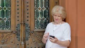 Elderly woman using smartphone with earphones. Vintage building in the background. stock footage