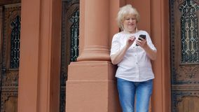 Elderly woman using smartphone with earphones. Vintage building in the background. stock video footage