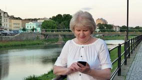 Elderly woman using smartphone near the railing on waterfront in evening time, old city, river and bridge in the stock footage