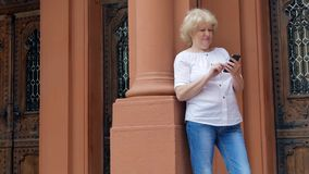 Elderly woman using smartphone. Vintage building in the background. stock video