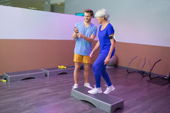 Elderly woman using stepper for fitness. Elderly women using a stepper for fitness Royalty Free Stock Images