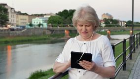 Elderly woman using tablet computer with earphones near the railing on waterfront in evening time, old city, river and. Bridge in the background stock video