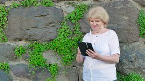 Elderly woman using tablet computer with earphones. Vintage wall of wild stone in the background. stock video