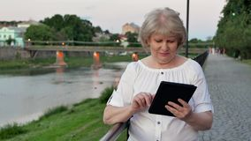 Elderly woman using tablet computer near the railing on waterfront in evening time, old city, river and bridge in the. Background stock video