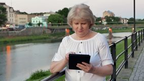 Elderly woman using tablet computer near the railing on waterfront in evening time, old city, river and bridge in the. Background stock footage