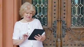 Elderly woman using tablet computer. Vintage building in the background. Elderly woman using tablet computer. Vintage building in the background stock video