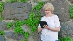 Elderly woman using tablet computer. Vintage wall of wild stone in the background. Elderly woman using tablet computer. Vintage wall of wild stone in the stock footage