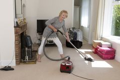 Senior woman using a vacuum during a housework session Royalty Free Stock Photo