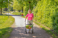 Elderly woman using a walker to do her shopping Royalty Free Stock Photos