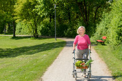 Elderly woman using a walker to do her shopping Stock Photos