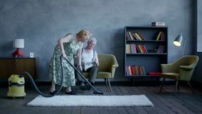 Elderly woman vacuuming the floor, and an elderly man reading a newspaper.  stock footage