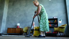 Elderly woman vacuuming the floor, and an elderly man reading a newspaper and drink vine.  stock footage