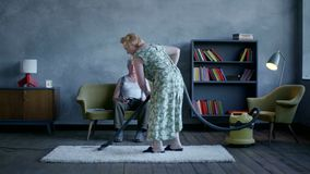 Elderly woman vacuuming the floor, and an elderly man reading a newspaper and watch television stock footage