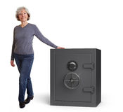 Elderly woman with vault. Happy senior woman leaning on a safe vault stock photography
