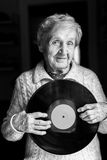 Elderly woman with vinyl lp disc in her hands. Royalty Free Stock Photography