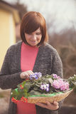 Elderly woman with violet flowers Royalty Free Stock Photos