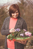 Elderly woman with violet flowers Royalty Free Stock Images