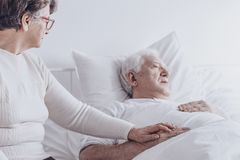 Elderly woman visiting sick husband. Elderly women visiting sick husband suffering from back pain while lying in bed at hospital Stock Photos