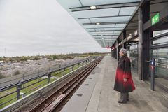 An elderly woman is waiting for a train on a ground metro Royalty Free Stock Image