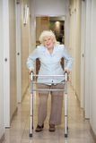 Elderly Woman With Walker In Hospital Corridor. Full length portrait of an elderly woman with walker standing in hospital corridor Royalty Free Stock Photos