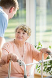 Elderly woman with a walker. Elderly women with a walker assisted by a nurse Royalty Free Stock Image
