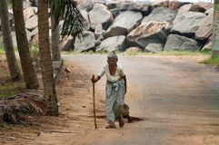Elderly woman walking along the road in the fishing village Stock Photography