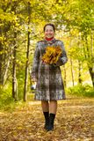 Elderly woman  walking in autumn park Royalty Free Stock Images