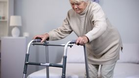 Elderly woman with walking frame, medical equipment using after trauma, hospital stock photo
