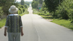 Elderly woman walking on the road in the village stock video