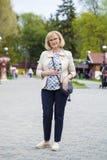 Elderly woman walking in spring park Royalty Free Stock Photo