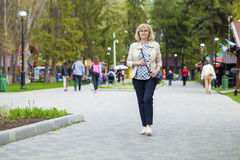 Elderly woman walking in spring park Royalty Free Stock Image