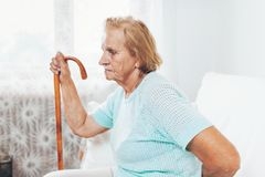 Elderly woman with a walking stick. Elderly woman in the 80s with a walking stick royalty free stock images