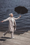 Elderly woman walking with umbrella on riverside at daytime. Casual elderly woman walking with umbrella on riverside at daytime Stock Photo