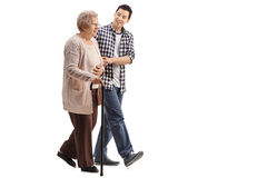 Elderly woman walking with a young man. Full length profile shot of an elderly women with a walking cane walking with a young men isolated on white background Royalty Free Stock Photos