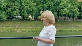 Elderly woman walks along the waterfront and using smartphone with earphones. River in the background. stock footage