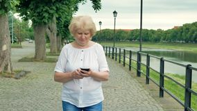 Elderly woman walks along the waterfront and using smartphone. River in the background. stock video footage